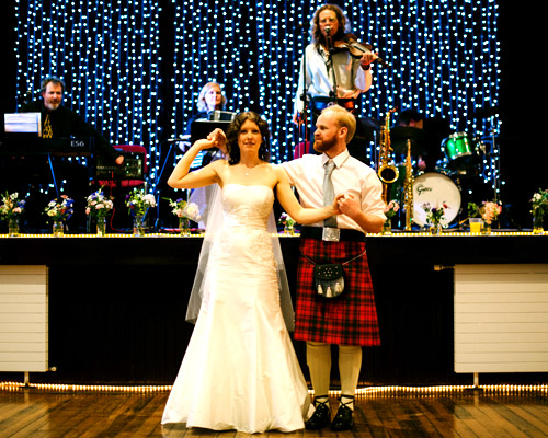 Bride & Groom with Funkeilidh Band on stage behind